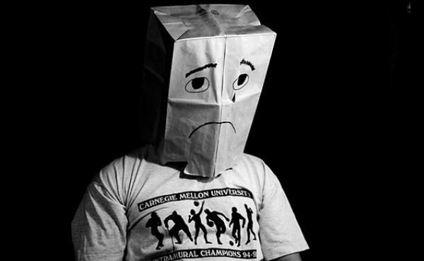 Грустный человек с коробкой на голове